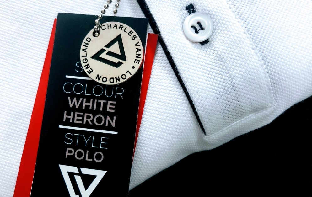 close up of folded charles vane white heron polo shirt with clothes tag.
