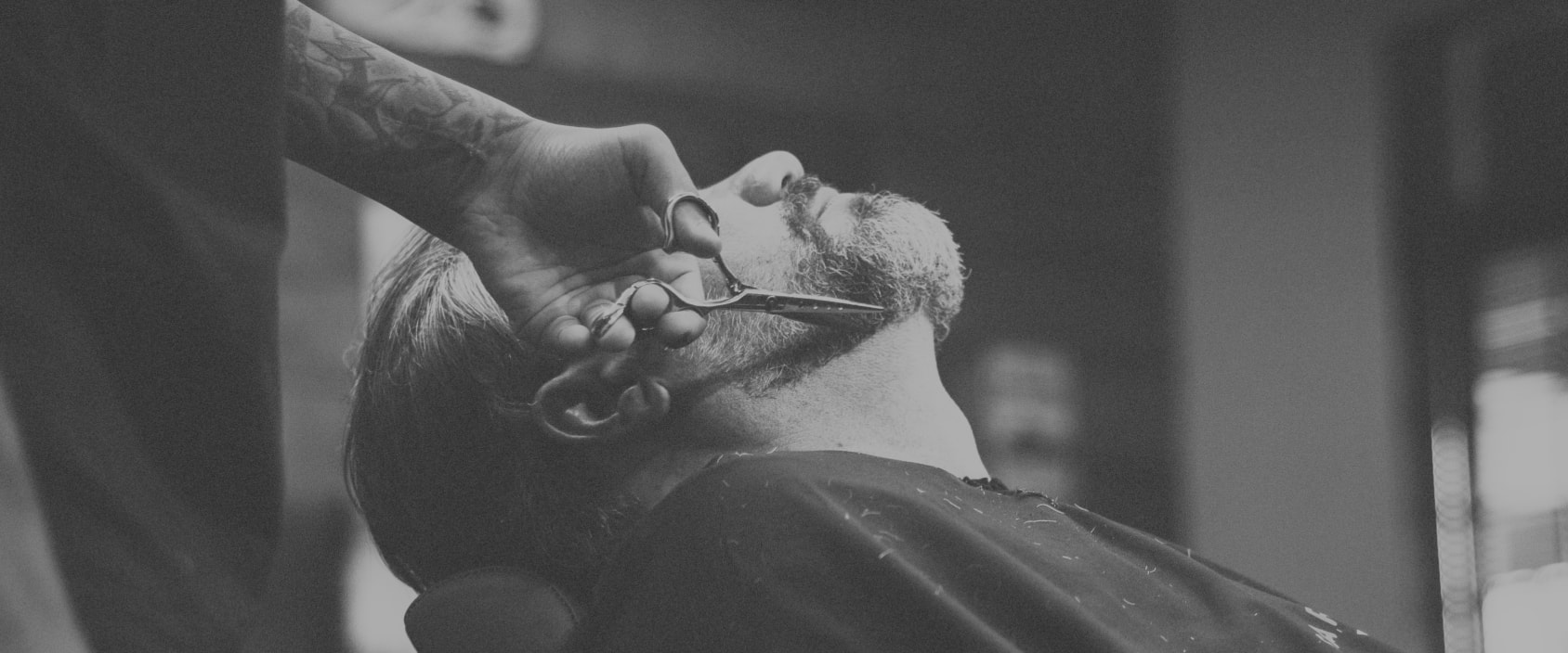 man getting his beard trimmed with scissors in barber chair