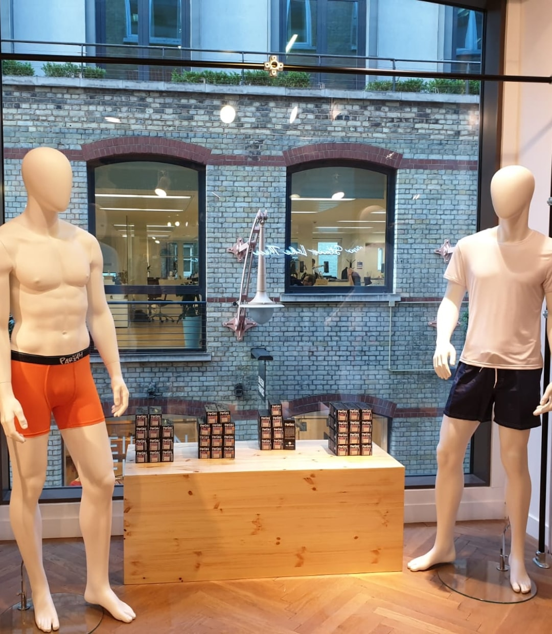 a male mannequin wearing orange pariah underwear. a male mannequin wearing white t-shirt and beach shorts.
