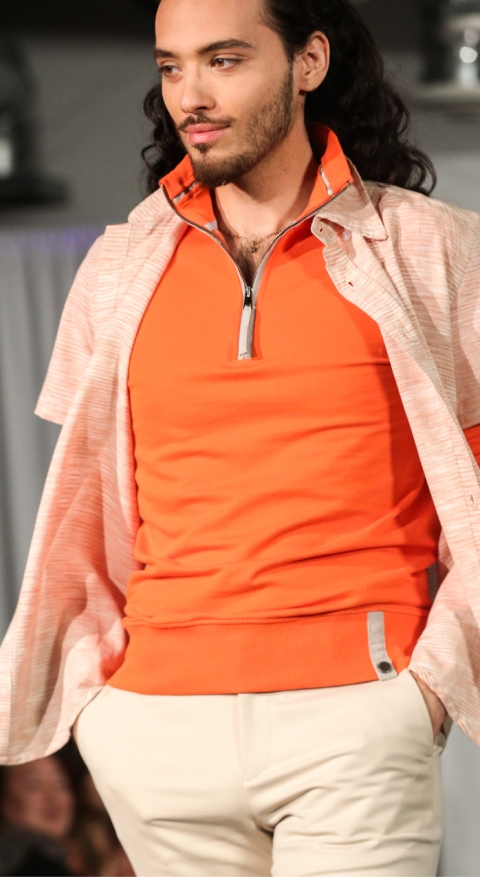 model wearing orange half zip sweatshirt and kaki pants