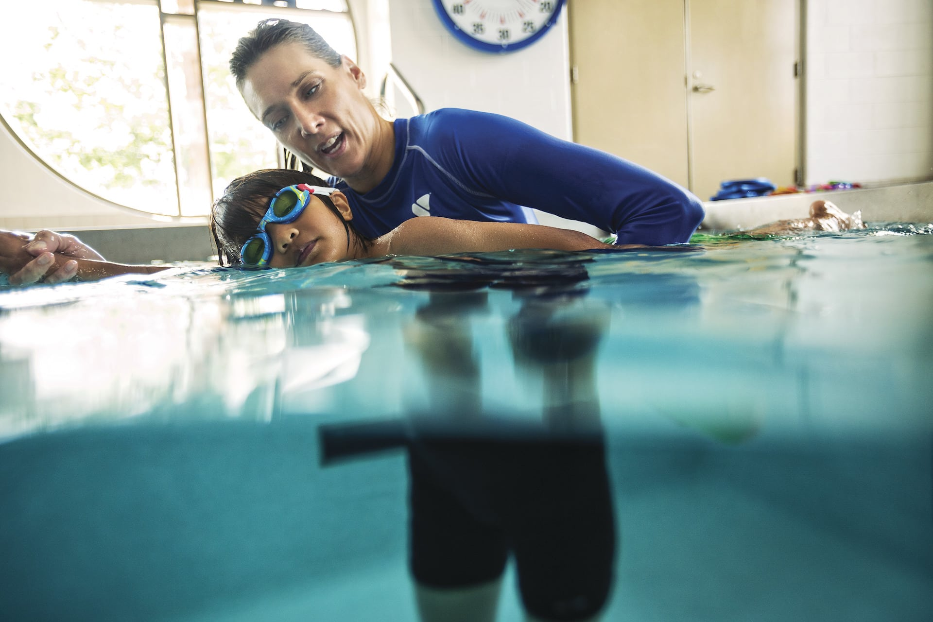 Swimming instructor doing an hands-on stroke exercise with a young swimmer.