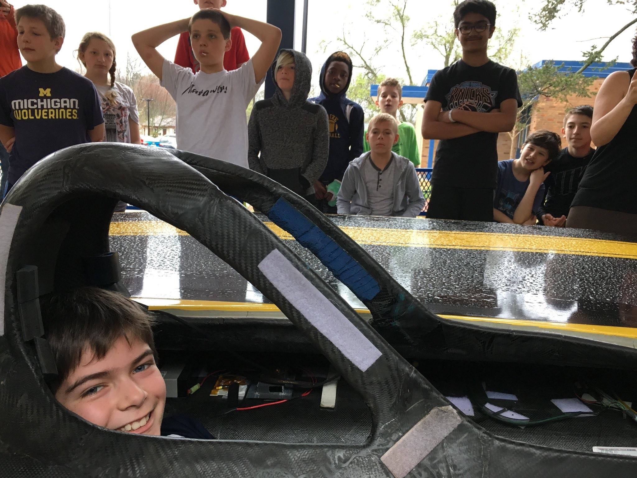 image of child in solar car while visiting a school