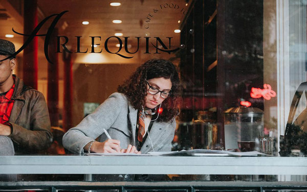 A woman sitting in a cafe and writing something on paper