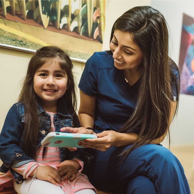 Photo of a female team member with a young patient looking at a phone
