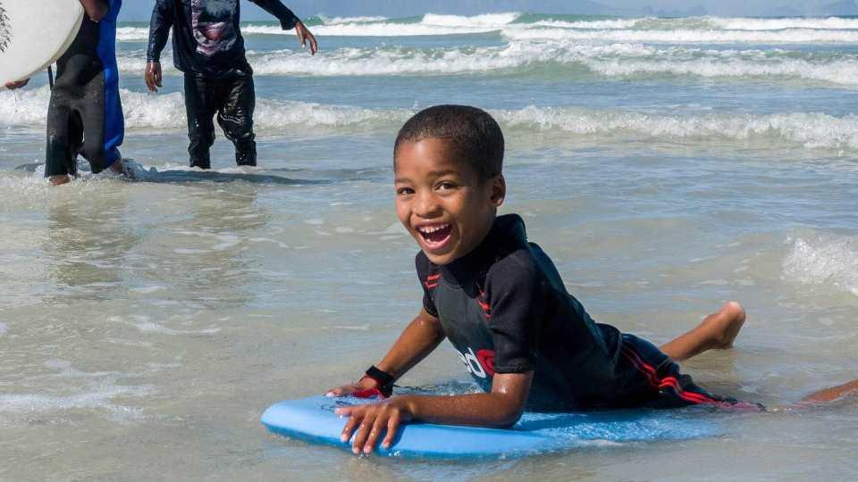 glücklicher Junge beim Surfen