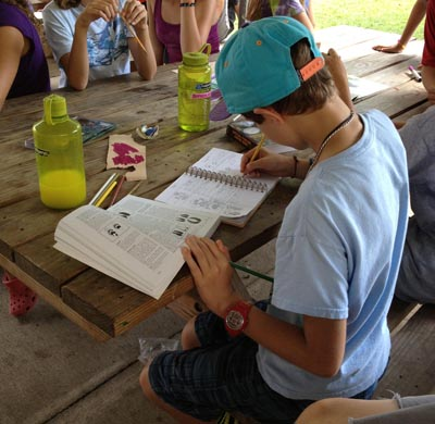 Camper taking notes at picnic table