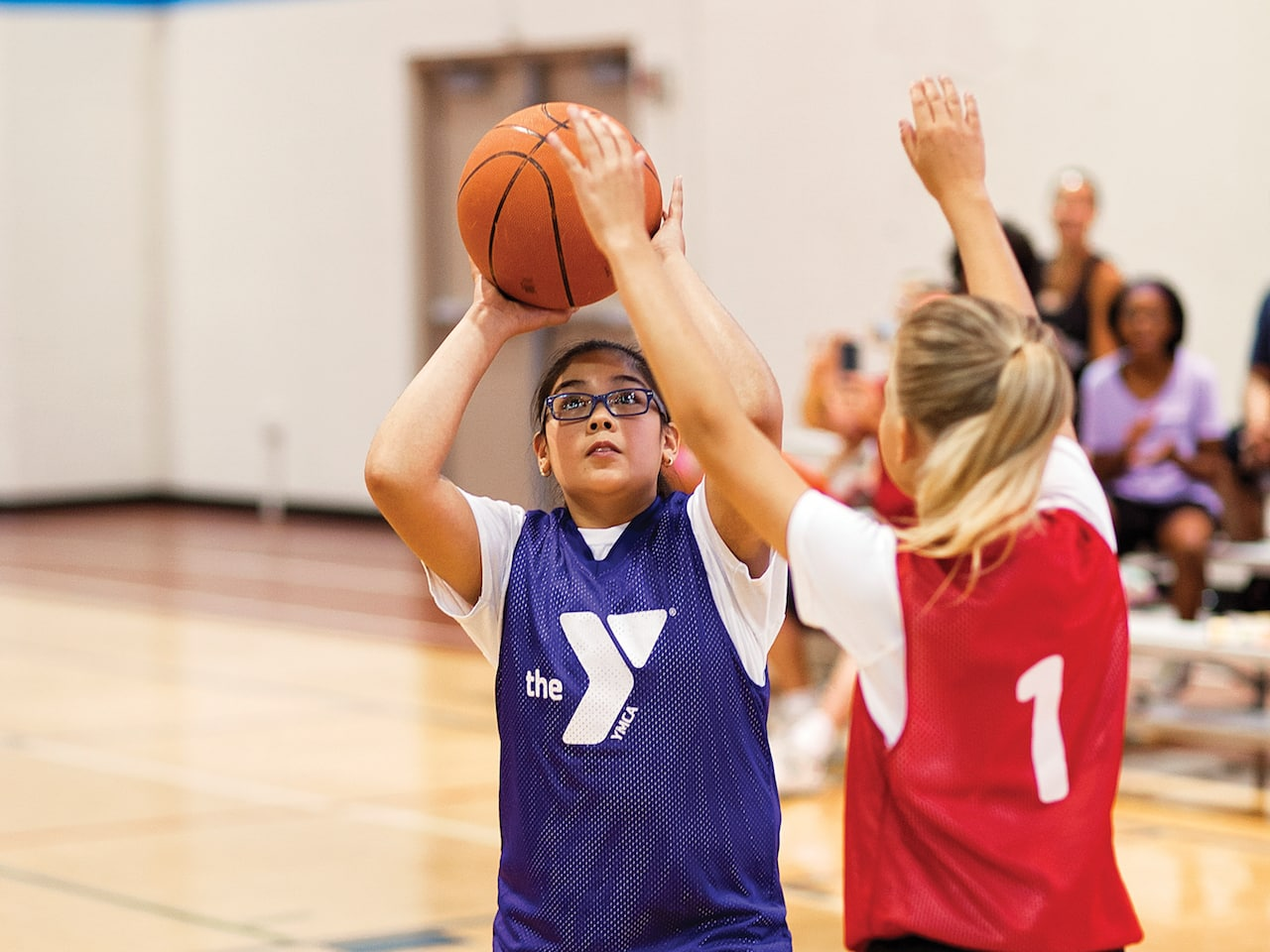 A young girl shooting around a defender trying to block her shot.