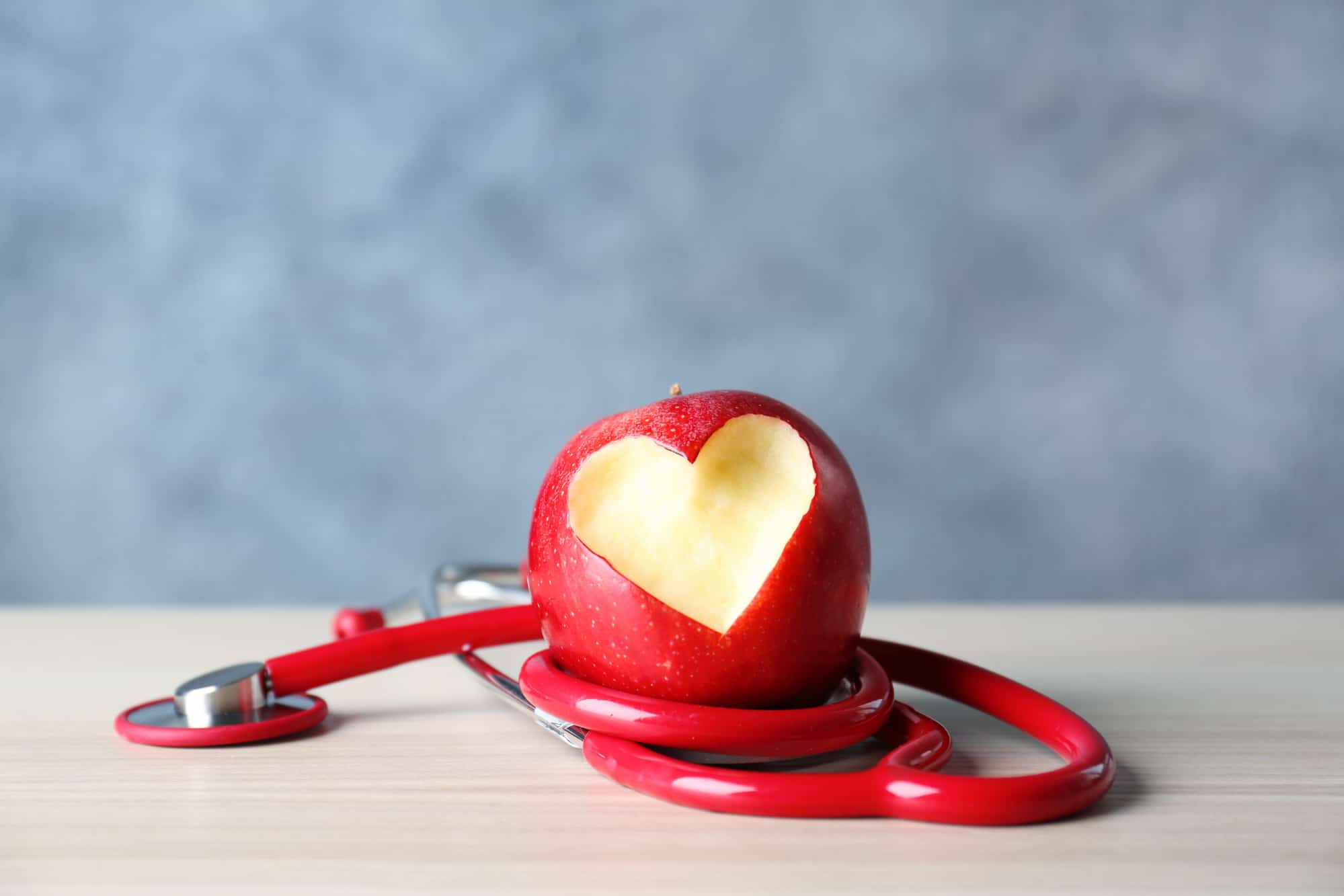 Stethoscope wrapped around a red apple.