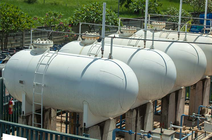 three gray storage tanks