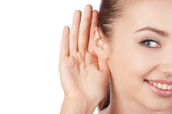 Young woman with hearing loss has her hand cupped behind her right ear to improve sound reception.