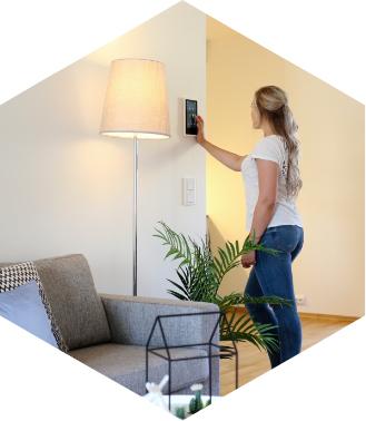 Bilde av en kvinne som bruker et styringspanel til å se hvem som står utenfor døren