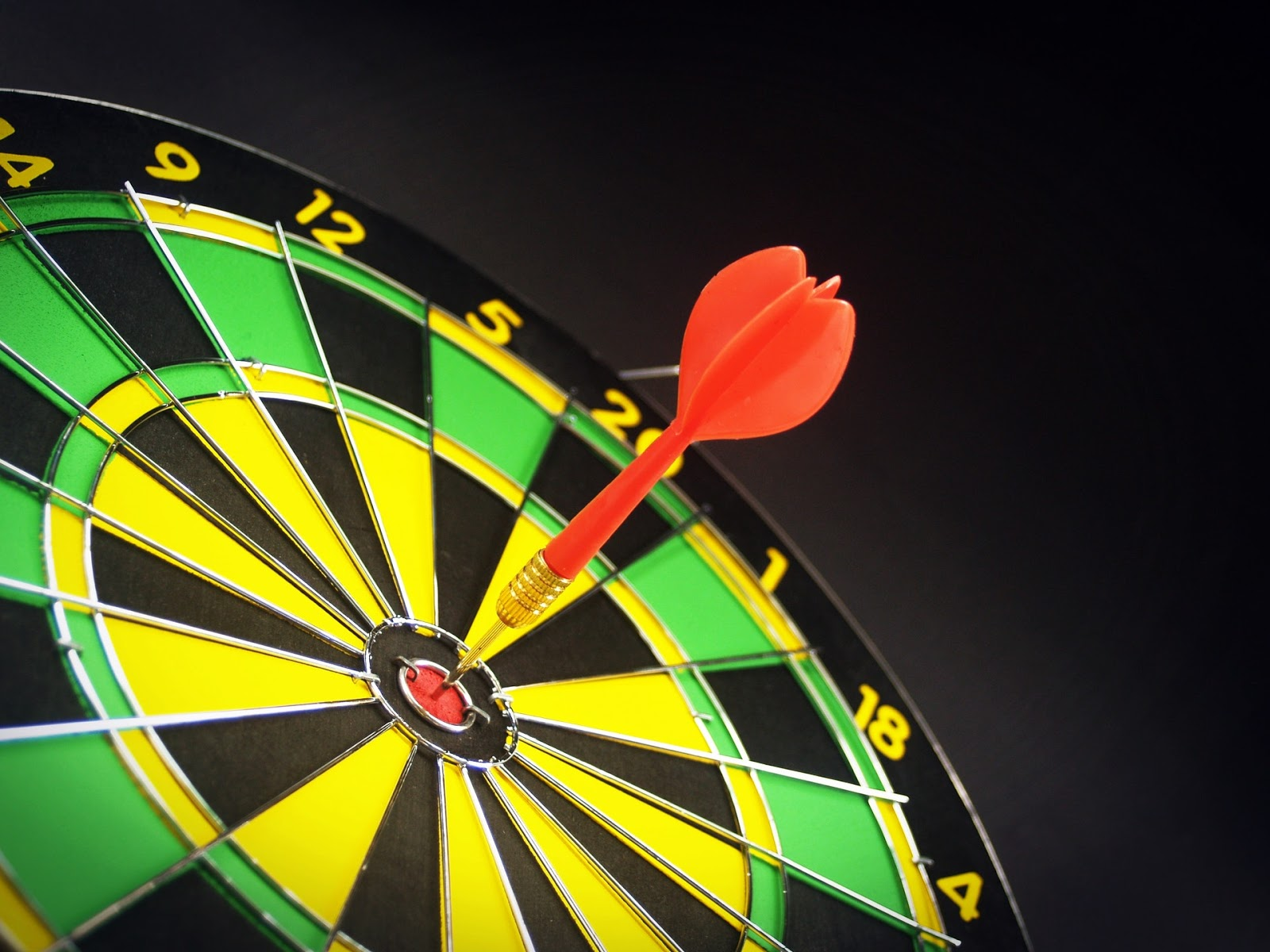 black and yellow dartboard with red dart