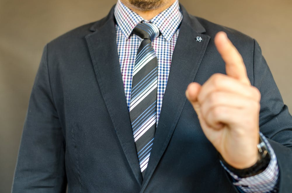 man in business suit pointing finger up