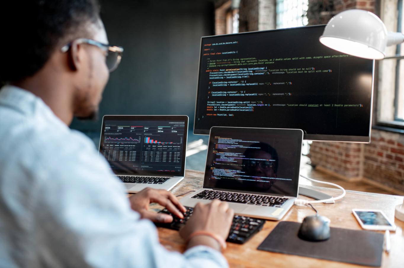 man coding on 3 different monitors