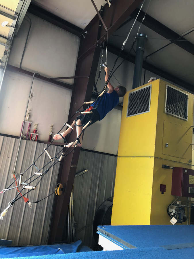 Boy climbing rope ladder