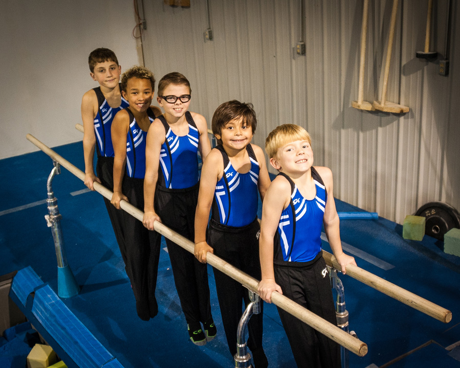 Boys team posing on parallel bars
