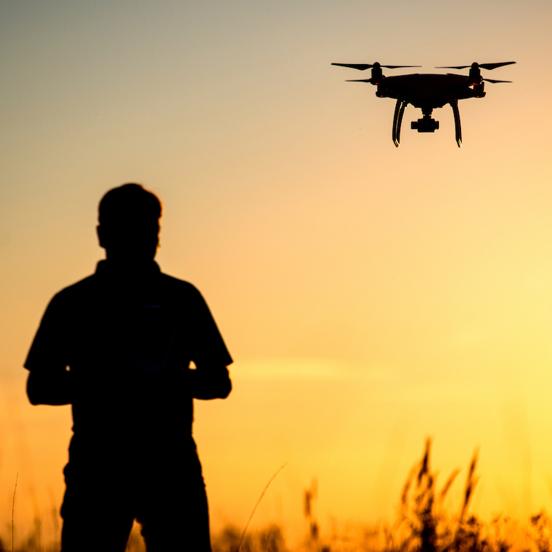 Image of person flying a drone at sunset.