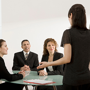 Image of female presenting at a meeting.