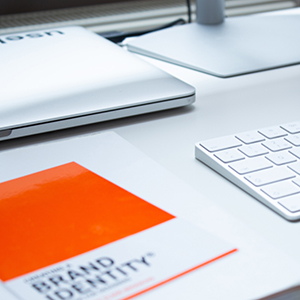 Image of brand identity book on table with keyboard.