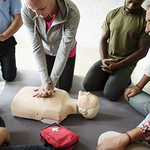 Image of female performing CPR on training dummy.