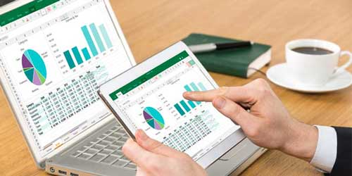 photo of computer and tablet with spreadsheet displayed