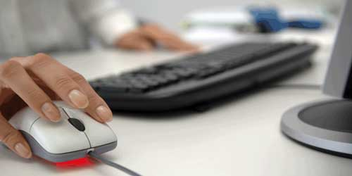 Image of a person clicking a mouse in front of a computer
