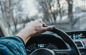 Image of a hand on a steering wheel driving
