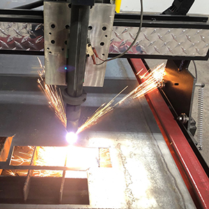 Image of the plasma cutter making a cut with a bright light where the cut is occuring.