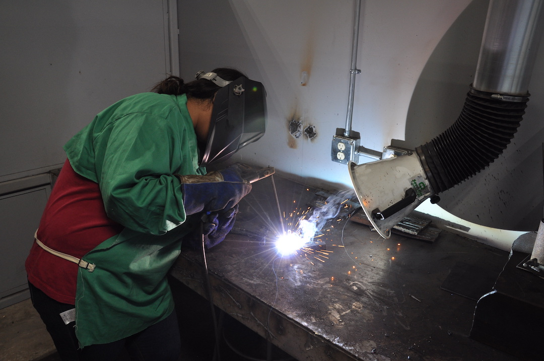 Image of student welding on table.