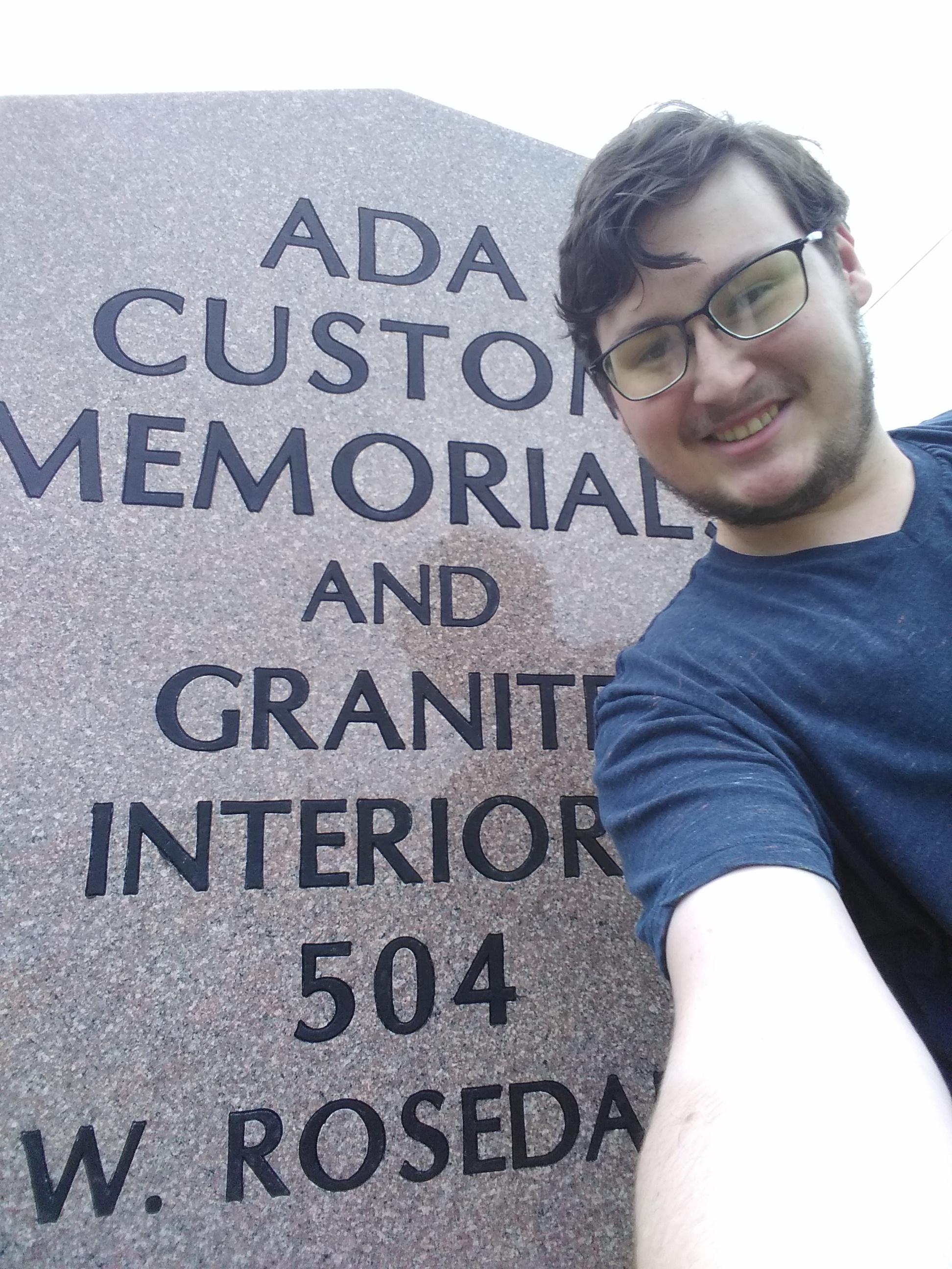 Photo of David Balliet next to Ada Custom Memorial sign