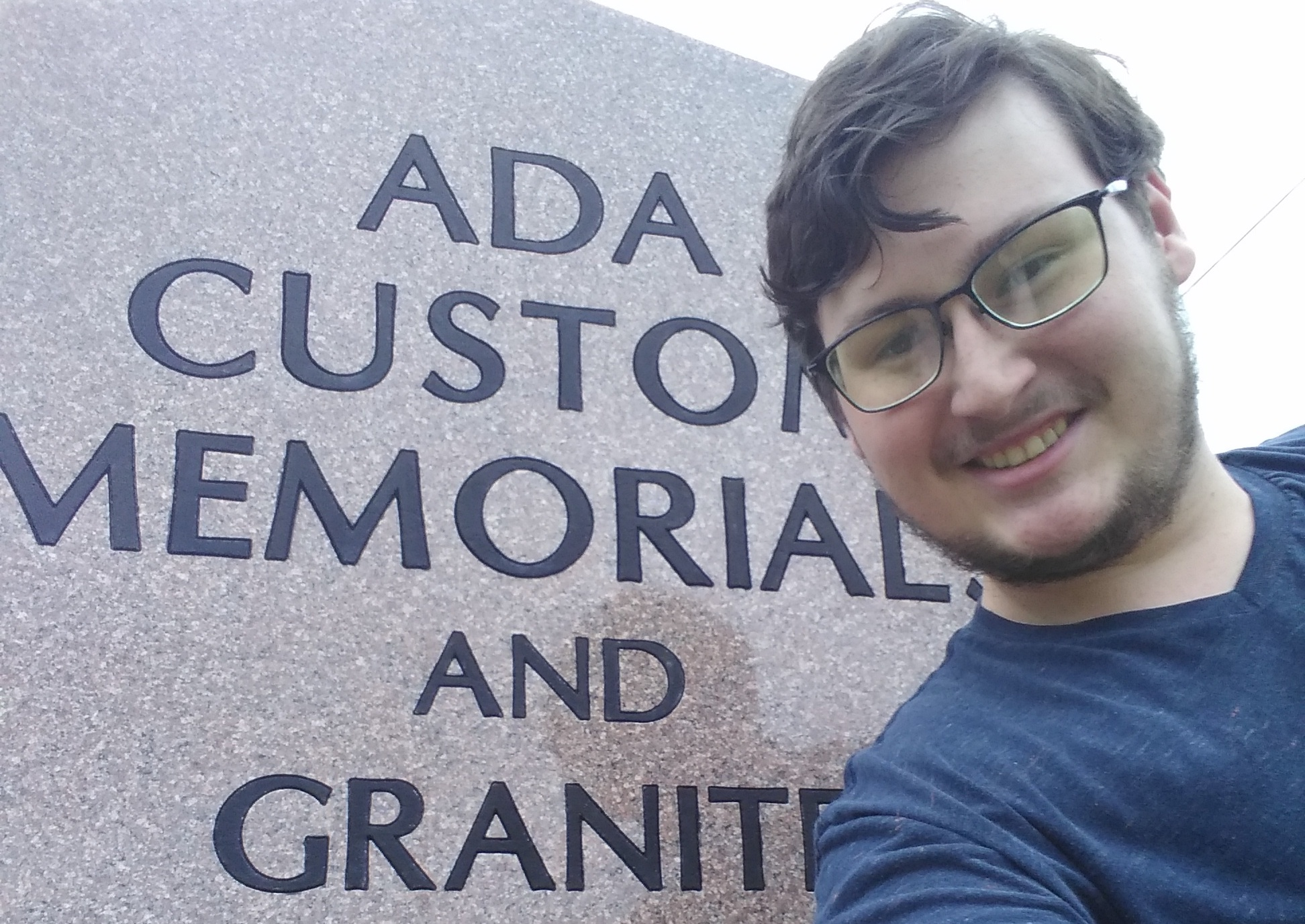 Photo of David Balliet next to Ada Custom Memorial and Granite sign