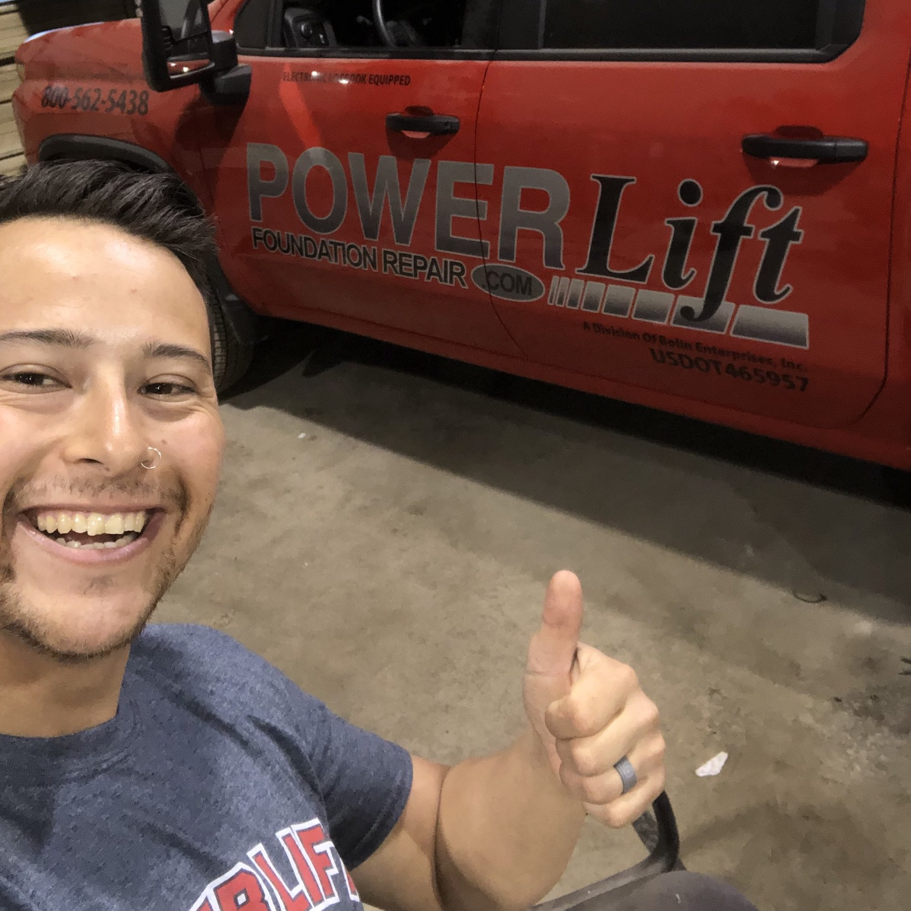 Image of Jordan giving a thumbs up in front of a red pickup.