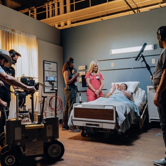 Photo showing filming on a movie set made to look like a hospital room.