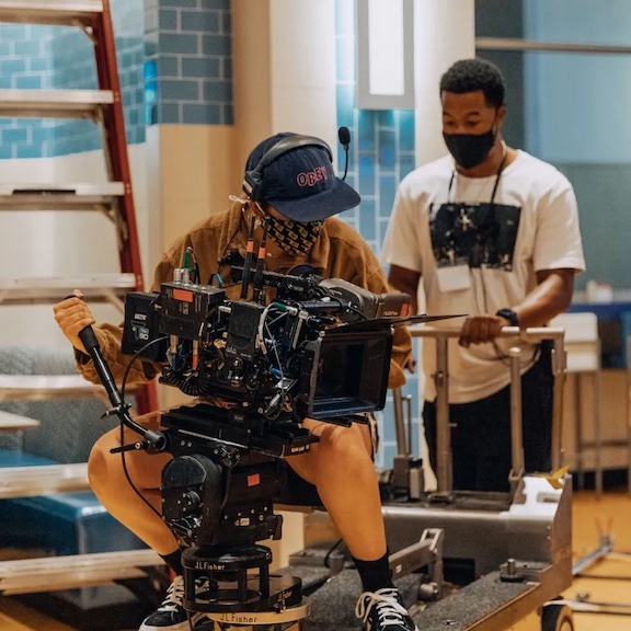 Man operating a movie camera on a track with an assistant helping