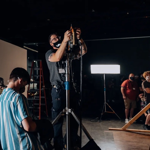 Lighting technician adjusting film lighting equipment