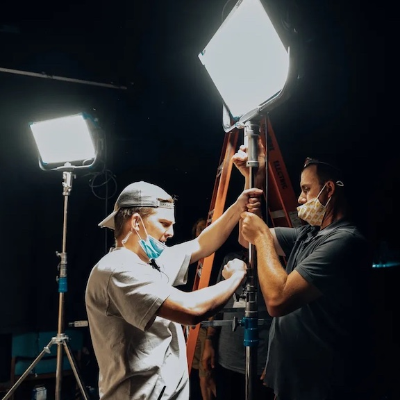 People setting up video lighting.