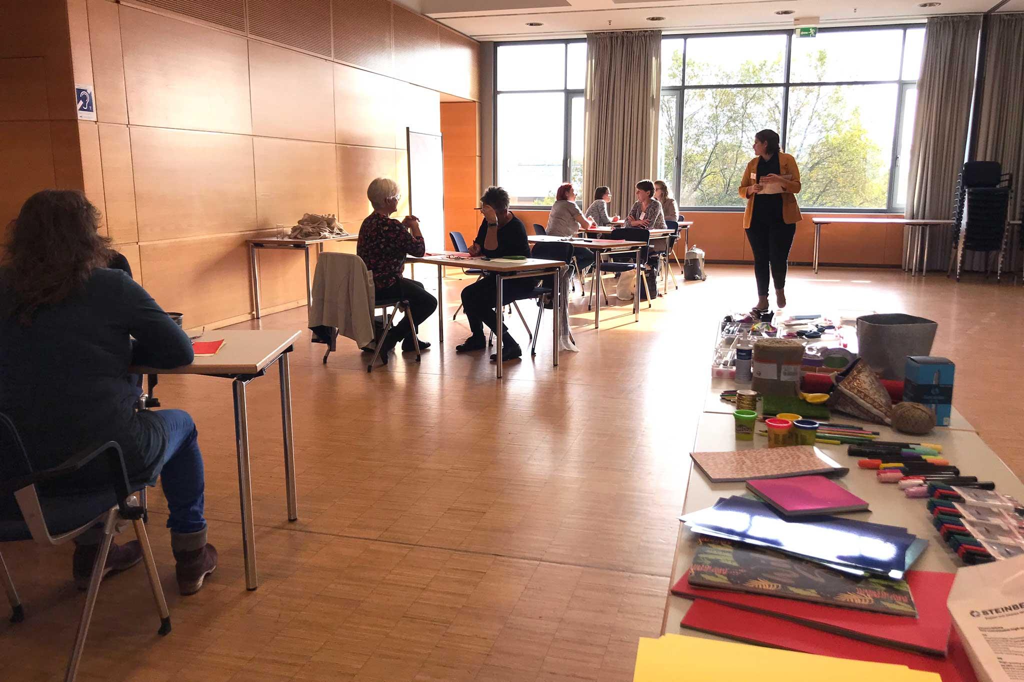 Workshopbild vom Design Thinking. Teilnehmer an ihrem Arbeitsplatz, Tisch mit Material für die Prototypen.