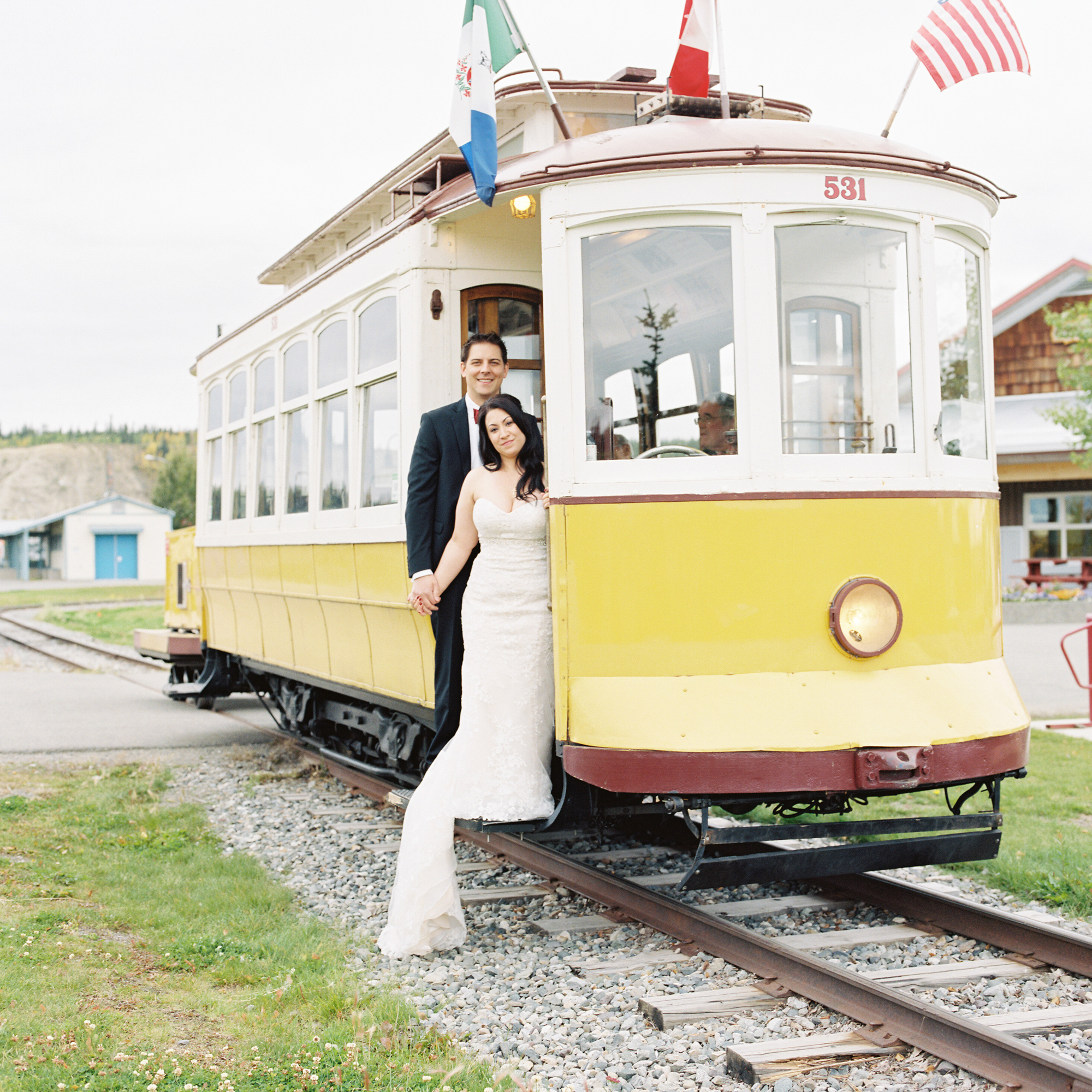 Portrait of newly married couple standing in train car downtown Whitehorse, Yukon