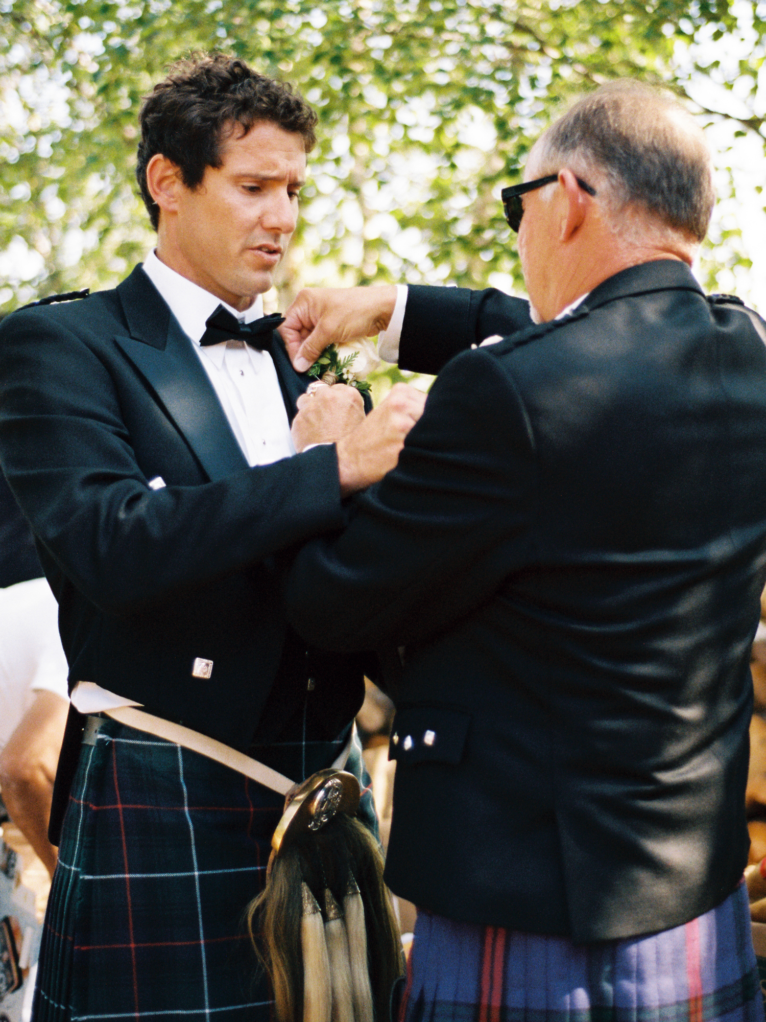Father and son pinning corsage