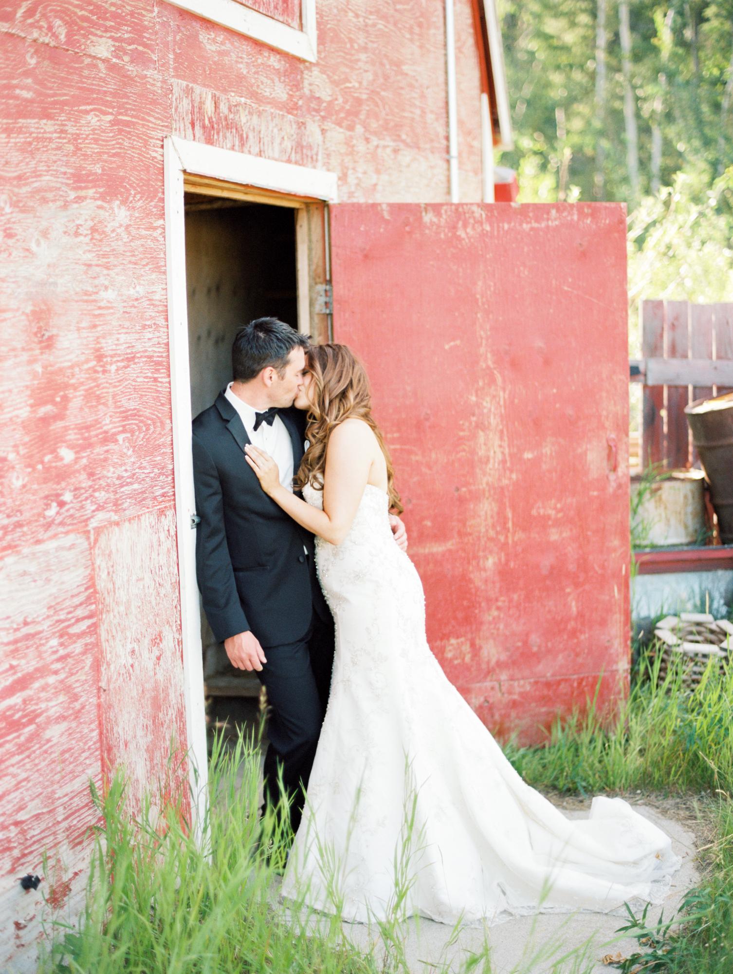 Bride and groom kissing at rustic barn