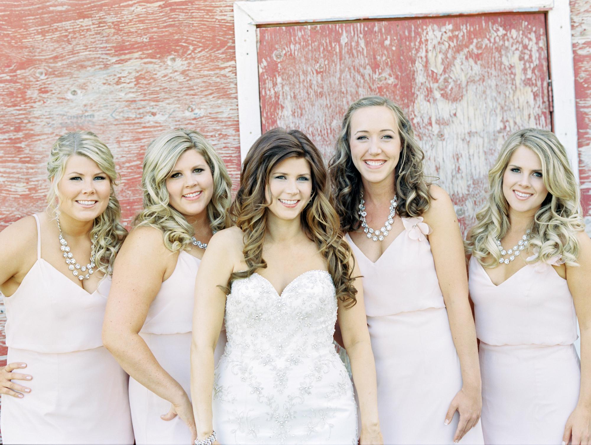 Bride and bridesmaids at rustic red barn