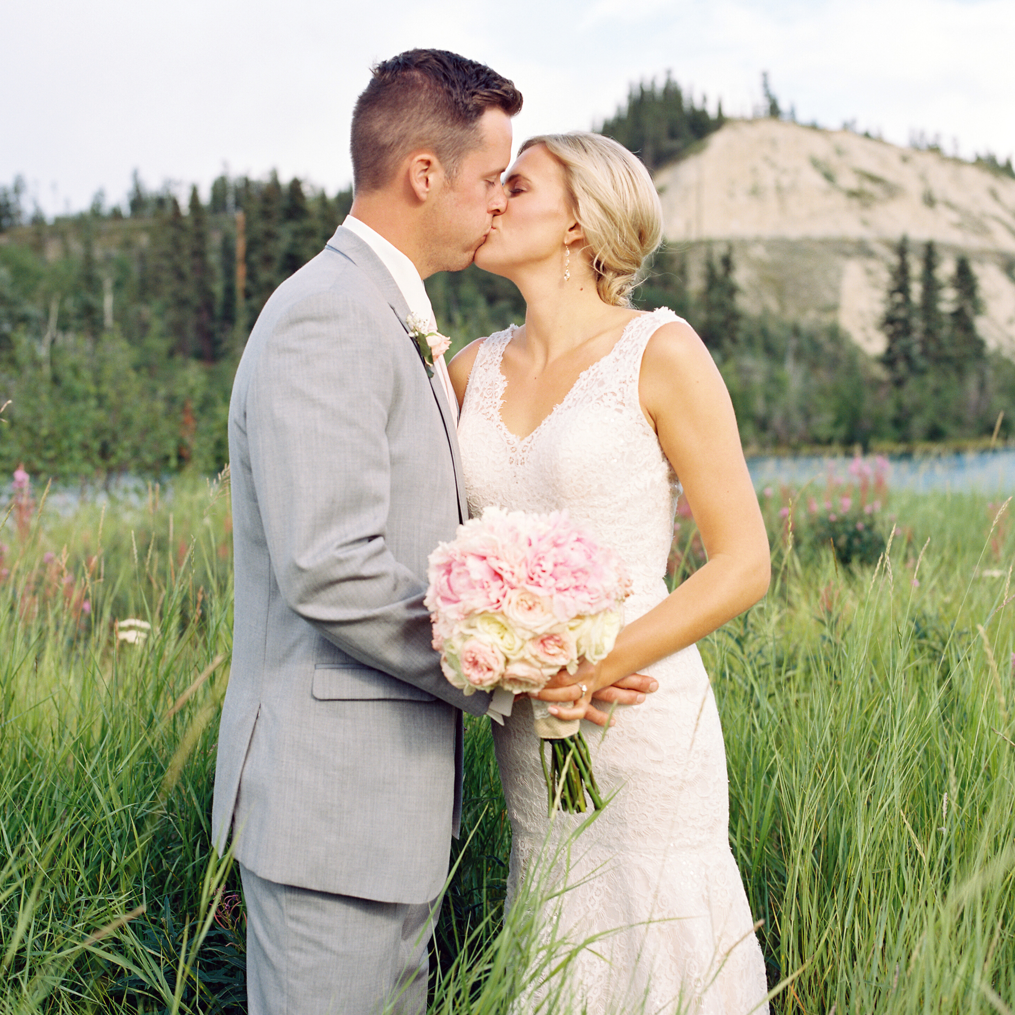 Bride and groom kissing near the Yukon river