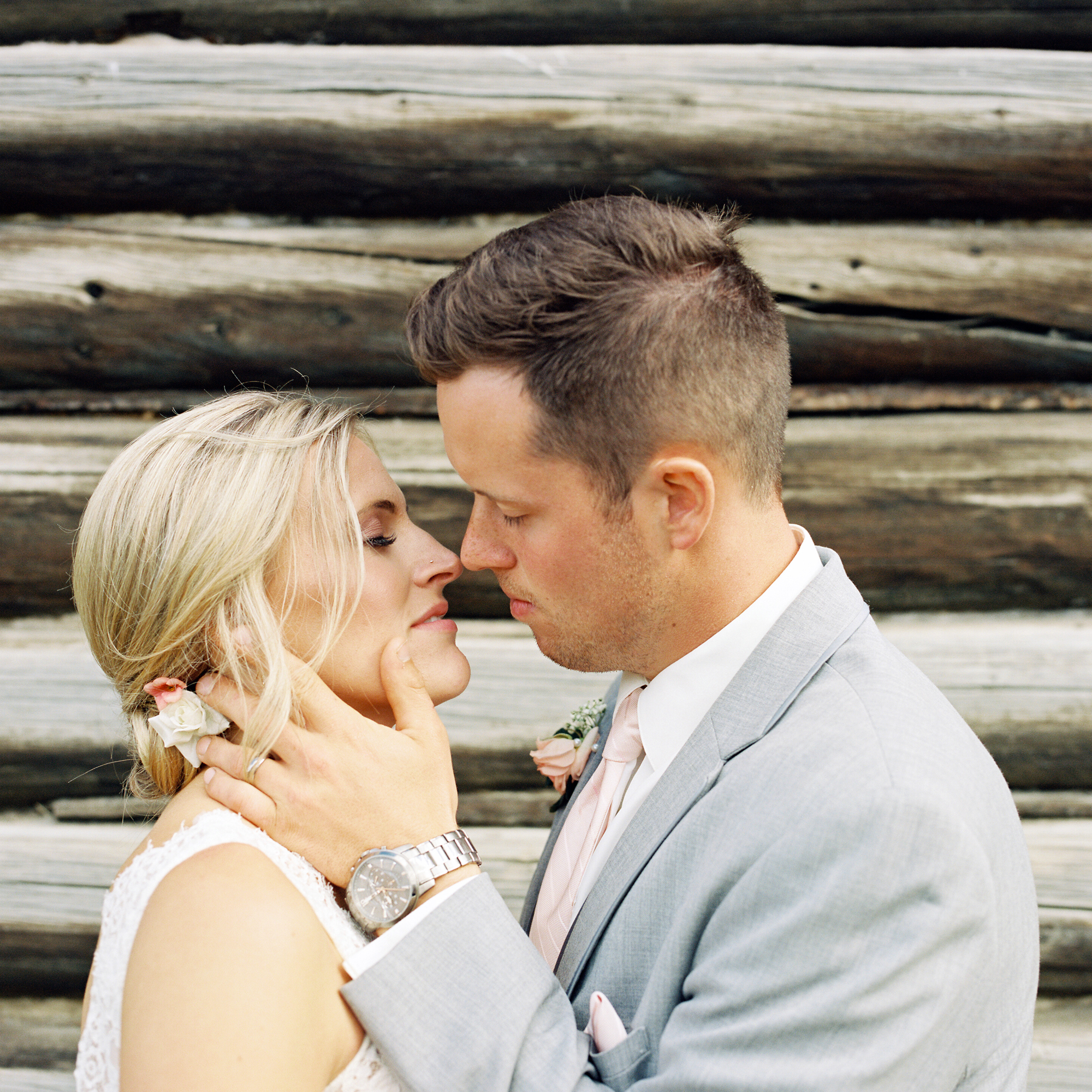 Bride and groom kiss in front of log cabin in Whitehorse, Yukon