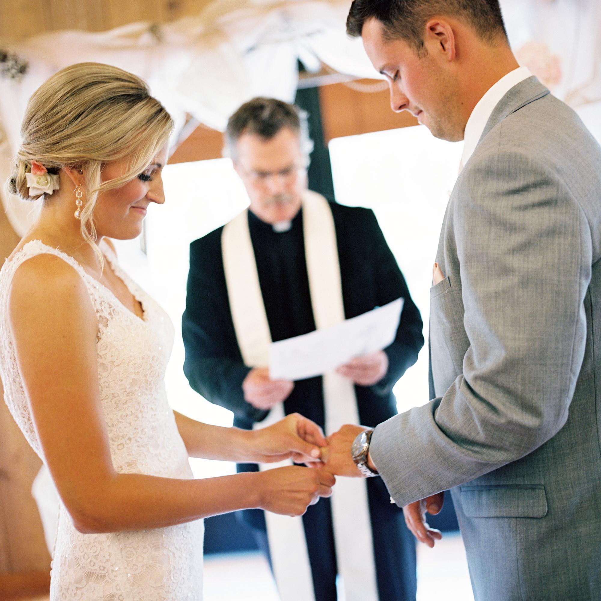 Bride putting on grooms wedding ring