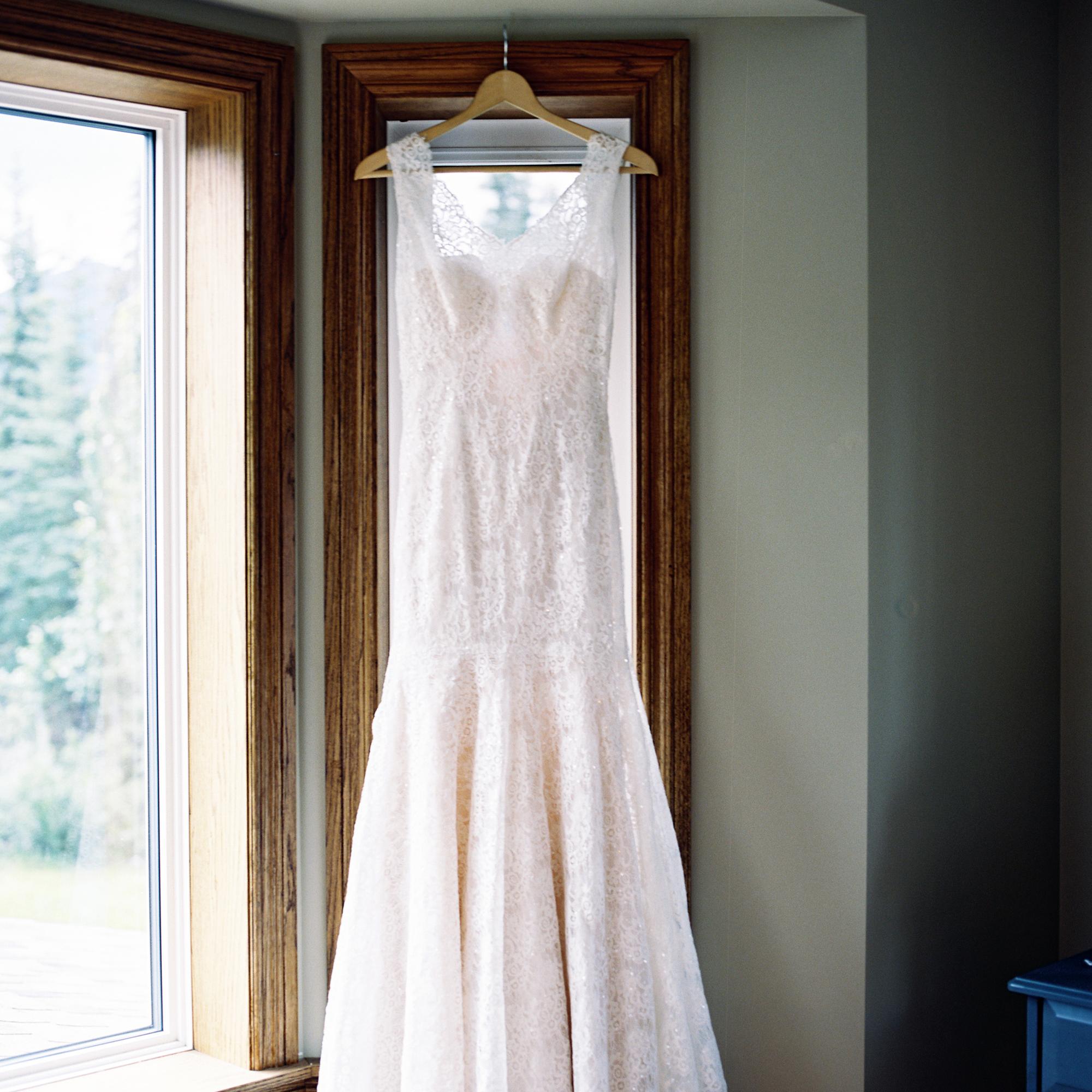 Wedding dress hanging in front of window
