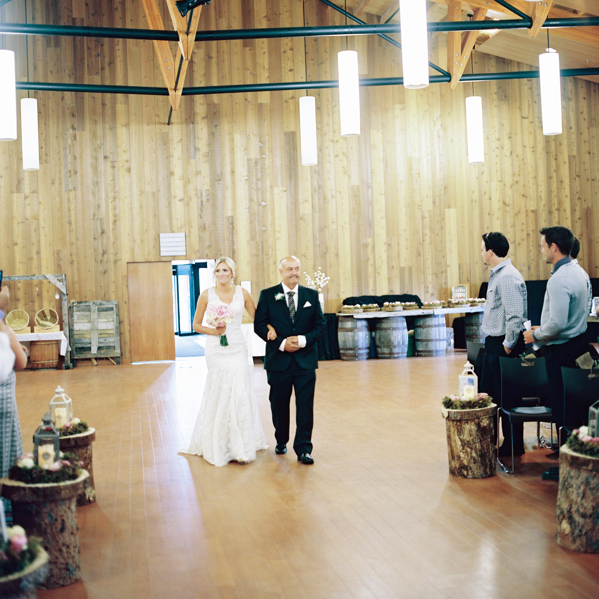 Bride and Father walking down aisle in the Kwanlin Dün Cultural Centre in Whitehorse, Yukon