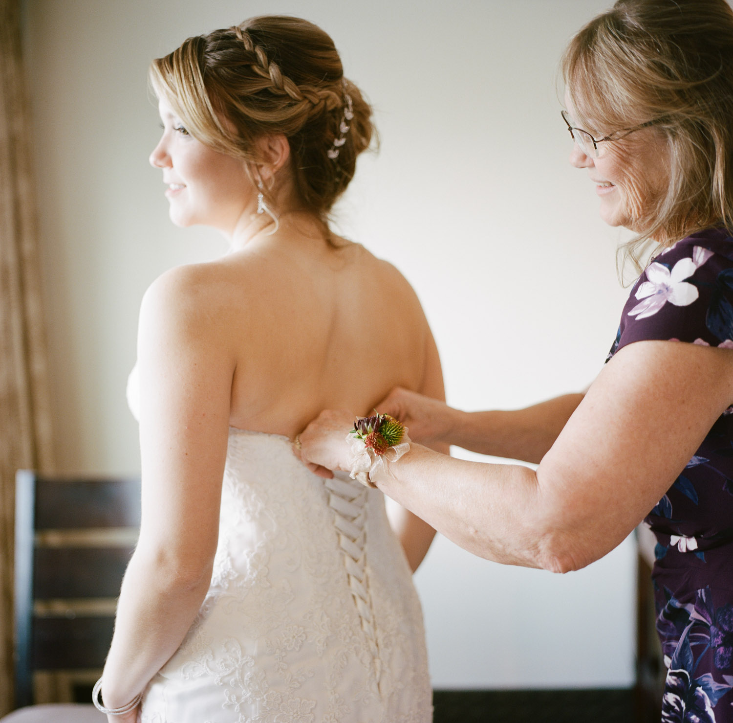 Mother of bride helping daughter with wedding dress in Kamloops at Hotel 540 wedding