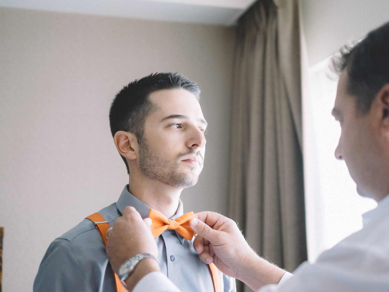 Father of groom helping with bow tie  in Kamloops at Hotel 540 wedding.