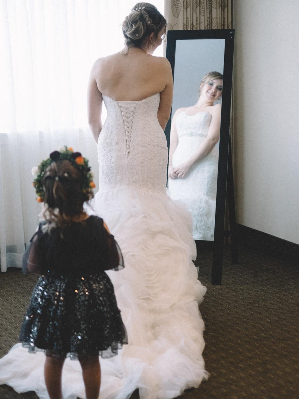 Bride looking back at flower girl in mirror in Kamloops at Hotel 540 wedding
