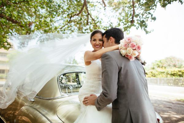 Brautpaar neben einem Oldtimer